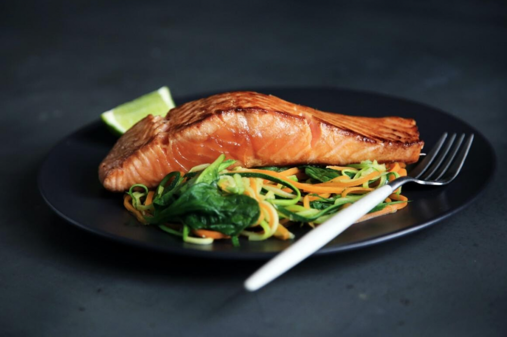 healthy salmon protein over a bed of greens